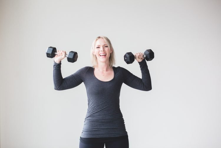 Happy woman lifting dumbbells - Three vital tips for the beginner's fitness journey blog